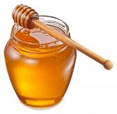 Glass can full of honey and wooden stick on it. Clipping paths.