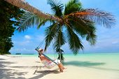 pic of swing  - Young beautiful woman relaxing in swing hanging on coconut palm at tropical beach - JPG