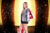 Stylish blonde holding shopping bags against glittering screen on black background