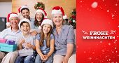Extended family in Christmas hats with gift boxes in living room against red vignette