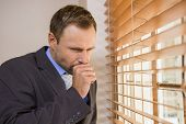 foto of cough  - Businessman looking out the window and coughing - JPG