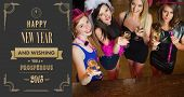 Happy gorgeous women holding flutes of champagne having hen party against art deco new year greeting