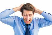 Stressed businessman with hands on head on white background