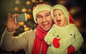 Selfie  In Christmas. Happy Family Dad Playing With Daughter And Photographed On  Mobile Phone