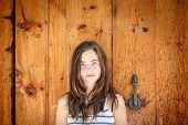 Portrait Of A Beautiful Teenage Girl In Front Of An Ancient Wood Door