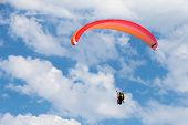 Red Paraglider In The Blue Sky With Clouds