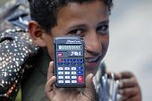 young market seller demonstrates calculator to bargain the price in Sana'a, Yemen.