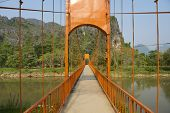 Pedestrian bridge across Nam Song river in tourist oriented town of Vang Vieng, Laos.