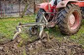 picture of plow  - Image from the back of a tractor plowing the land focus is on plow - JPG