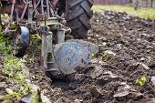 stock photo of plow  - Image from the back of a tractor plowing the land focus is on plow - JPG