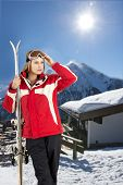 young, pretty woman posing with her skis in front of a hill top restaurant in a ski resort