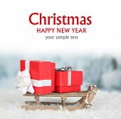 Wooden toy sledge with Christmas gifts on light background