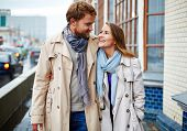 picture of trench coat  - Portrait of affectionate couple in trench coats walking and talking - JPG