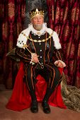 King in tudor costume sitting on his throne holding his scepter