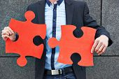 Business man holding two oversized red jigsaw puzzle pieces