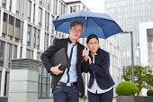 Two business people walking in the rain under an umbrella in the city