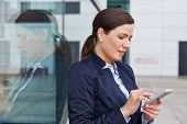Business woman looking at her smartphone and checking her mails in the city