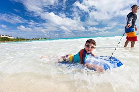 stock photo of boogie board  - Father and son surfing on boogie boards - JPG