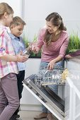 picture of dishwasher  - Happy mother and children placing glasses in dishwasher - JPG