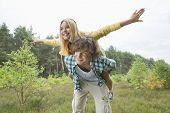 image of piggyback ride  - Happy woman enjoying piggyback ride on man in forest - JPG