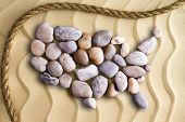 pic of memento  - Pebbles arranged in the shape of a map of the United Sates of America on decorative beach sand with wavy lines in an undulating pattern with a rope border in a nautical theme - JPG