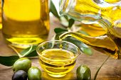 ������, ������: Olive Oil Bottle pouring Virgin Olive Oil in a bowl close up Olives and Healthy Olive oil being po