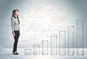 image of climb up  - Business woman climbing up on hand drawn graphs concept on background - JPG