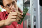 stock photo of ram  - Young asian shop owner working in computer store repairing computer and adding ram to pc. Focus on hand holding bank of RAM