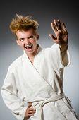 foto of karate  - Funny karate fighter wearing white kimono - JPG