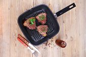 foto of bloody  - fresh grilled bloody beef steaks on black grill plate on wood - JPG