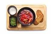 stock photo of condiment  - Russian borsht on a wooden plate served with sour cream green condiment and whole grain bread - JPG
