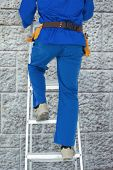 picture of step-ladder  - Low section of carpenter climbing step ladder against grey brick wall - JPG