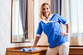 image of maids  - Image of happy maid dusting in hotel room - JPG