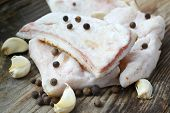 stock photo of pork belly  - White pork fat called salo with garlic and pepper on wooden kitchen table - JPG