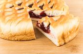 stock photo of cherry pie  - Cut cherry pie on wooden bamboo cutting board - JPG
