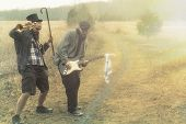 pic of gypsy  - Stylish gypsies play trumpet and electric guitar on a wilderness path in grainy old fashioned grunge photo - JPG