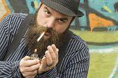 image of pimp  - Snazzy bearded man lights a cigarette on a city street - JPG