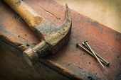 picture of work bench  - Old and worn contracting hammer and three nails on a distressed work bench - JPG