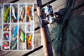 stock photo of fishing bobber  - Fishing Lures in tackle boxes with spinning rod and net on wooden pier - JPG