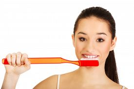 image of enormous  - Woman brushing her teeth with enormous brush - JPG