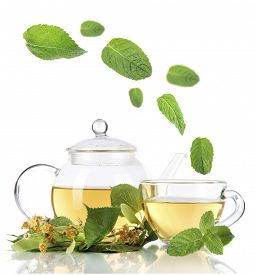 image of mint leaf  - Kettle and cup of tea with linden and falling mint leaves isolated on white - JPG