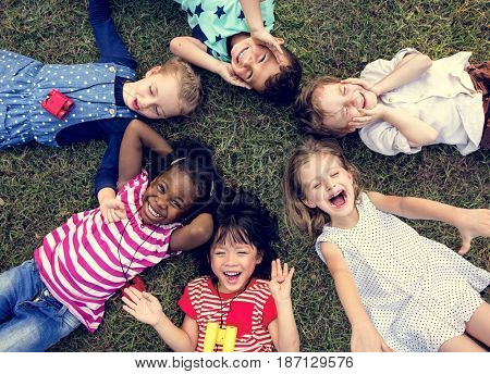 poster of Group of kindergarten kids lying on the grass at park and relax with smiling