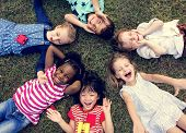 Group of kindergarten kids lying on the grass at park and relax with smiling poster