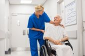 Nurse looking at elderly patient in a wheelchair in hospital ward. Doctor talking to old disabled in poster