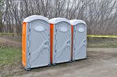 stock photo of porta-potties  - Three porta potties in park on spring day - JPG