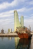 Bahrain financial harbor and a traditional fishing dhow.