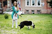 Trendy Girl At Glasses And Ripped Jeans With Russo-european Laika (husky) Dog On A Leash, Against St poster