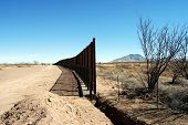 End of U.S.-Mexico border fence under construction in Arizona desert (U.S. to the left, Mexico to th