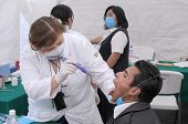 MEXICO CITY - APRIL 29: A doctor examines a flu patient for signs of Swine Flu at a clinic on April