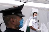 MEXICO CITY - APRIL 29: A police officer wears a face mask as he stands guard at a makeshift clinic